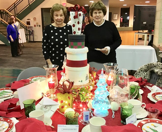 Sharon Price (left) and Mary Jane Russell enjoy their rummage sale table at the Advent by Candlelight event at the First United Methodist Church. Russell is chairperson of the rummage sale and had fun choosing items for the table.