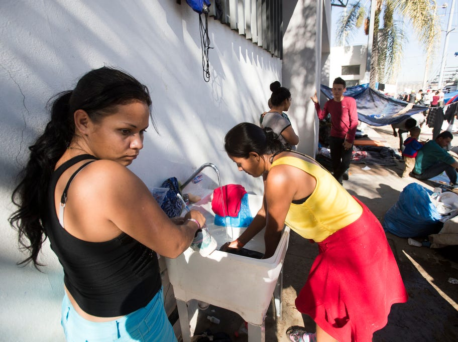 Women and men take turns to wash clothes in one of two sinks at the Benito Juarez sports complex shelter. The shelter had a maximum capacity of housing 3000 and is currently housing 5851 migrants inside the sports complex turned shelter in the city of Tijuana, Mexico on November 27, 2018.