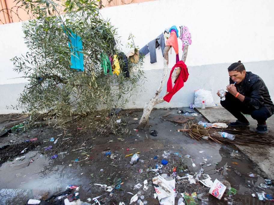 A migrants washes his teeth at the Benito Juarez sports complex shelter. The shelter had a maximum capacity of housing 3000 and is currently housing 5851 migrants inside the sports complex turned shelter in the city of Tijuana, Mexico on November 27, 2018.