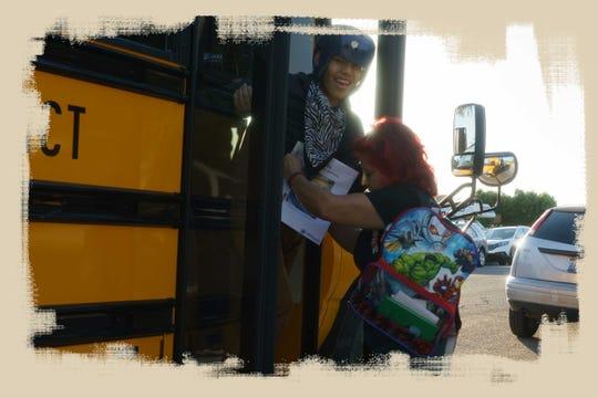 Candelaria Nieblas ayuda a su hijo Iván a descender del autobús escolar en Calexico.