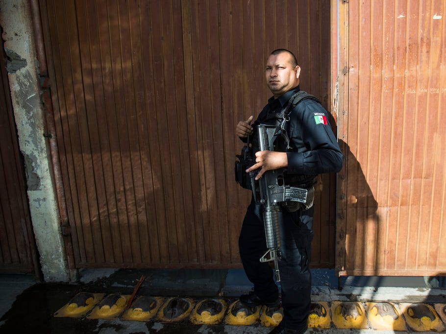 A Tijuana municipal police officer keeps members of the press from entering in what could be the second shelter for the caravan migrants on November 28, 2018. The 5000 migrants are currently housed in the Benito Juarez sports complex which had a maximum capacity of 3000. If the migrants agree to move to the new shelter, they would be moved 11 kilometers from the San Ysidro Port of Entry.