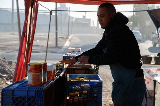 Luis Alberto Rodríguez lays out food at a street market in a neighborhood next to a row of factories in Mexicali.