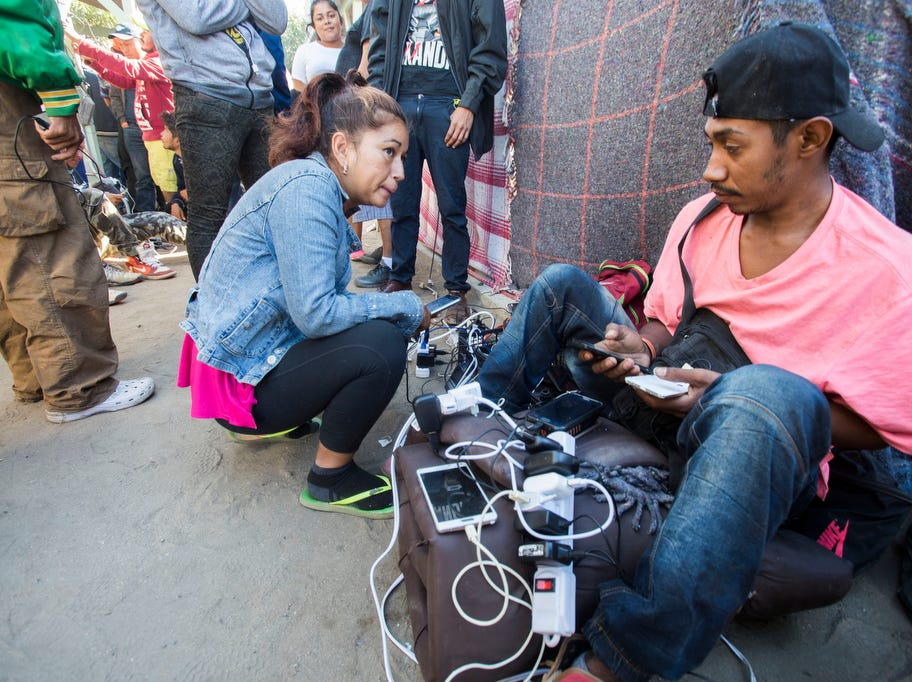 Migrants charge their phone batteries at the Benito Juarez sports complex shelter, which is housing more than 5000 migrants in the city of Tijuana, Mexico on November 27, 2018.
