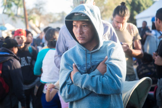 A migrant listens to his peers as they discuss the possibility of returning back to Honduras outside the Benito Juarez sports complex shelter, which is housing more than 5000 migrants in the city of Tijuana, Mexico.