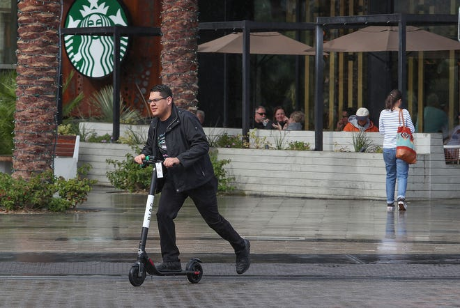 A man rides a Bird scooter in in the rain in downtown Palm Springs in November. On Dec. 13, 2018, the Palm Desert City Council approved a moratorium on all mobility sharing services, including e-scooters, until the city can develop regulations for the devices.