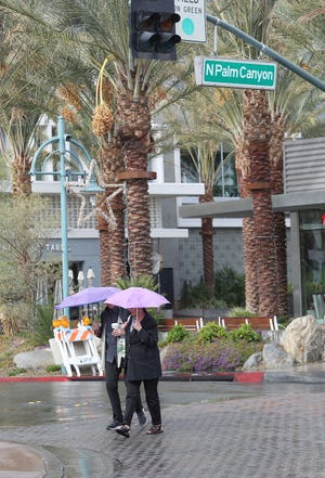 A couple makes their way through the rain in downtown Palm Springs, November 29, 2018.