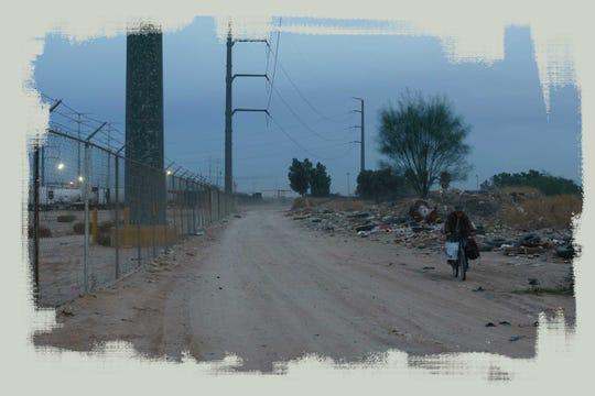 Un hombre en bicicleta transita por un camino adyacente a una fábrica en Mexicali.