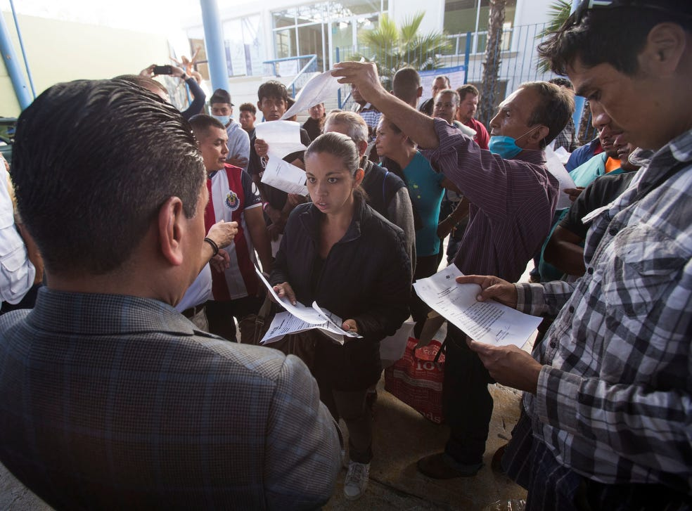 At far left, Honduran ambassador to Mexico, Alden Rivera Montes, listens to his compatriots during a job fair provided by the Tijuana municipal government for those migrants wishing to remain in Tijuana, Mexico on November 27, 2018.