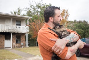 Sokka clings to Ryan Ward as he waits for his daughter Chloe to come home from school in Gulf Breeze on Thursday, November 29, 2018.  Sokka, who has been missing since a fire destroyed the Ward apartment, was found earlier in the day by Ryan when he stopped by to search for him among the ruin.