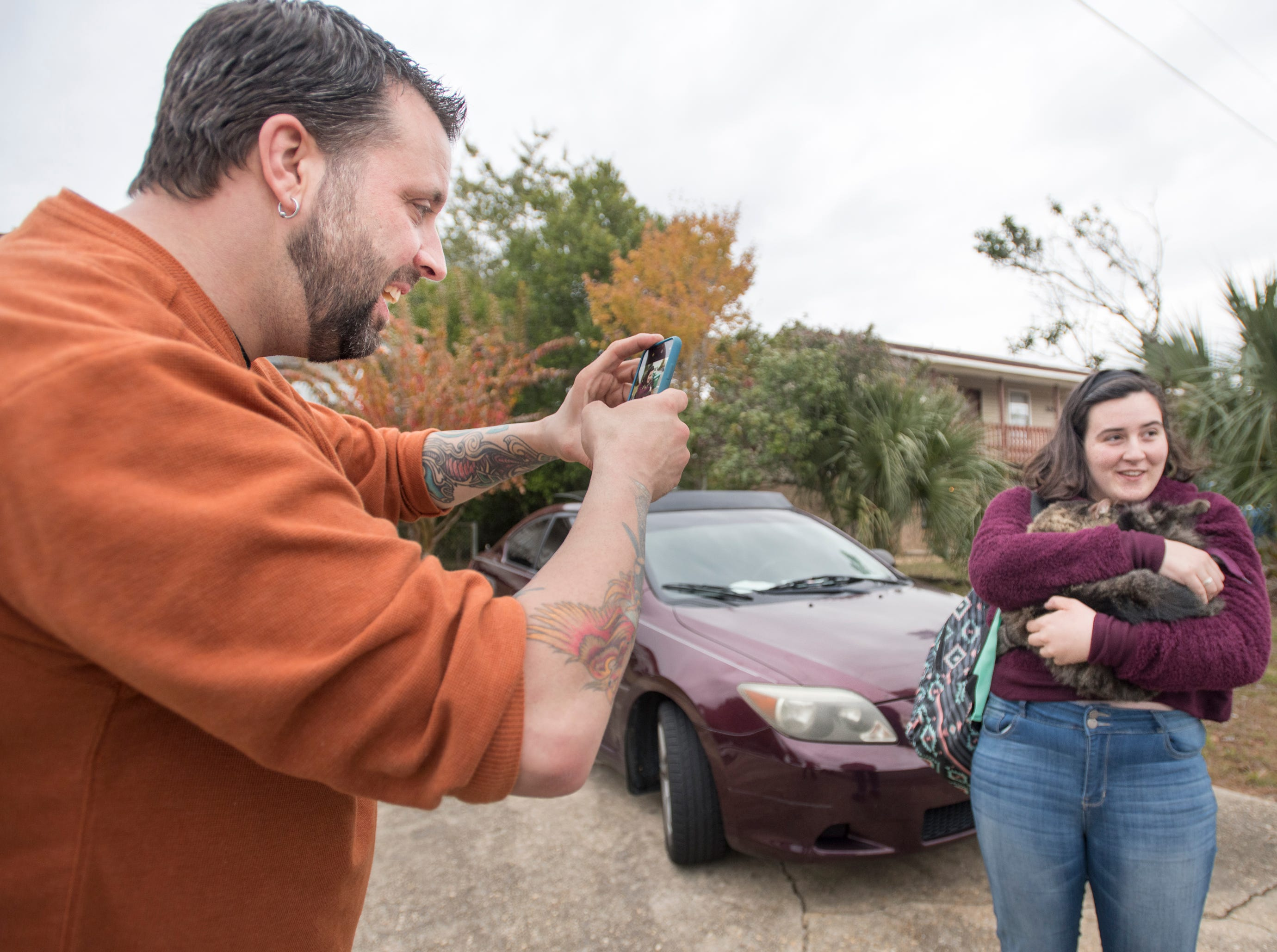 Ryan Ward snaps a photo of his daughter Chloe, 16, cuddling their cat Sokka after coming home from school in Gulf Breeze on Thursday, November 29, 2018.  Sokka, who has been missing since a fire destroyed the Ward apartment, was found earlier in the day by Ryan when he stopped by to search for him among the ruin.