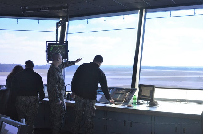 Air Traffic Controller 1st Class Christopher Reinhard trains AC3 Omer Dubose on helicopter movements and ground frequency at the NAS Whiting Field South Tower.