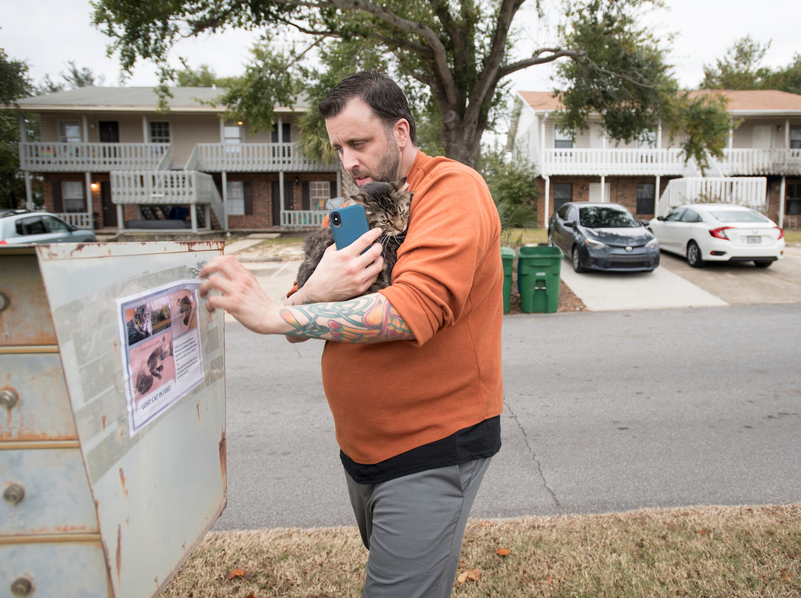 "Sokka clings to Ryan Ward as he removes a ""Lost Cat"" flyer near their home in Gulf Breeze on Thursday, November 29, 2018.  Sokka, who has been missing since a fire destroyed the Ward apartment, was found earlier in the day by Ryan when he stopped by to search for him among the ruin."