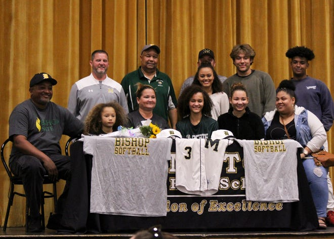 Milton High softball player Kiahna Connell (center) signed with Bishop (Ala.) State.