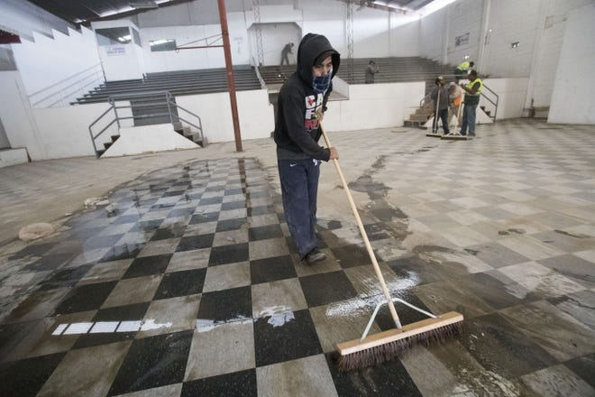 Crews on Nov. 28, 2018, clean up a building where a second shelter may be opened for caravan migrants. More than 6,100 migrants are currently housed in the Benito Juarez sports complex, which has a maximum capacity of 3,000. If the migrants agree to move to the new shelter, they would be moved 11 miles from the San Ysidro Port of Entry.