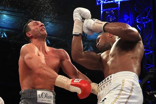Anthony Joshua catches Wladimir Klitschko, left, with a right hand during an IBF, WBA and IBO heavyweight world title bout April 29, 2017 at Wembley Stadium.