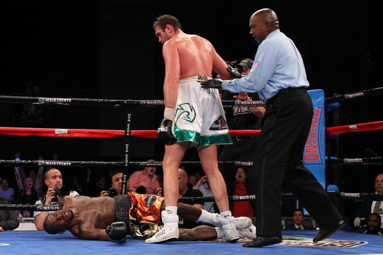 Tyson Fury stands over Steve Cunningham after delivering the knockout blow in the 7th round of their 12-round heavyweight fight April 20, 2013.