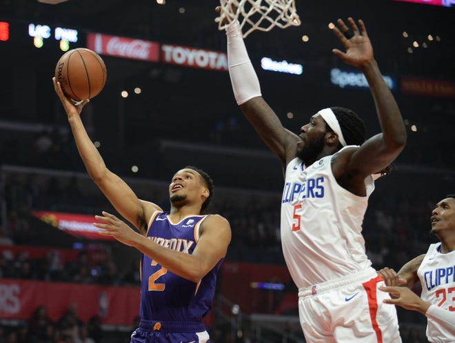 Suns guard Elie Okobo works his way to the basket ahead of Clippers forward Montrezl Harrell during the first half of a game at Staples Center.