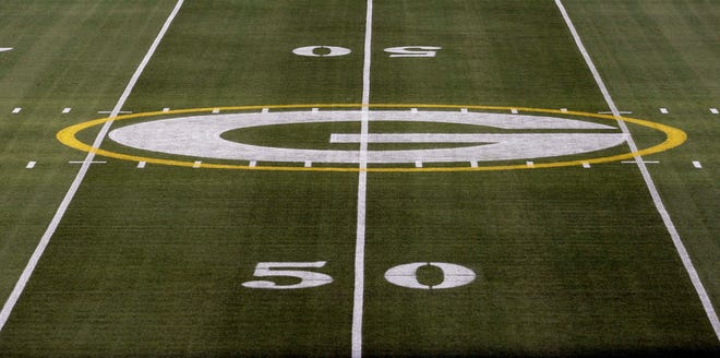 The Green Bay Packers logo at midfield at Lambeau Field.