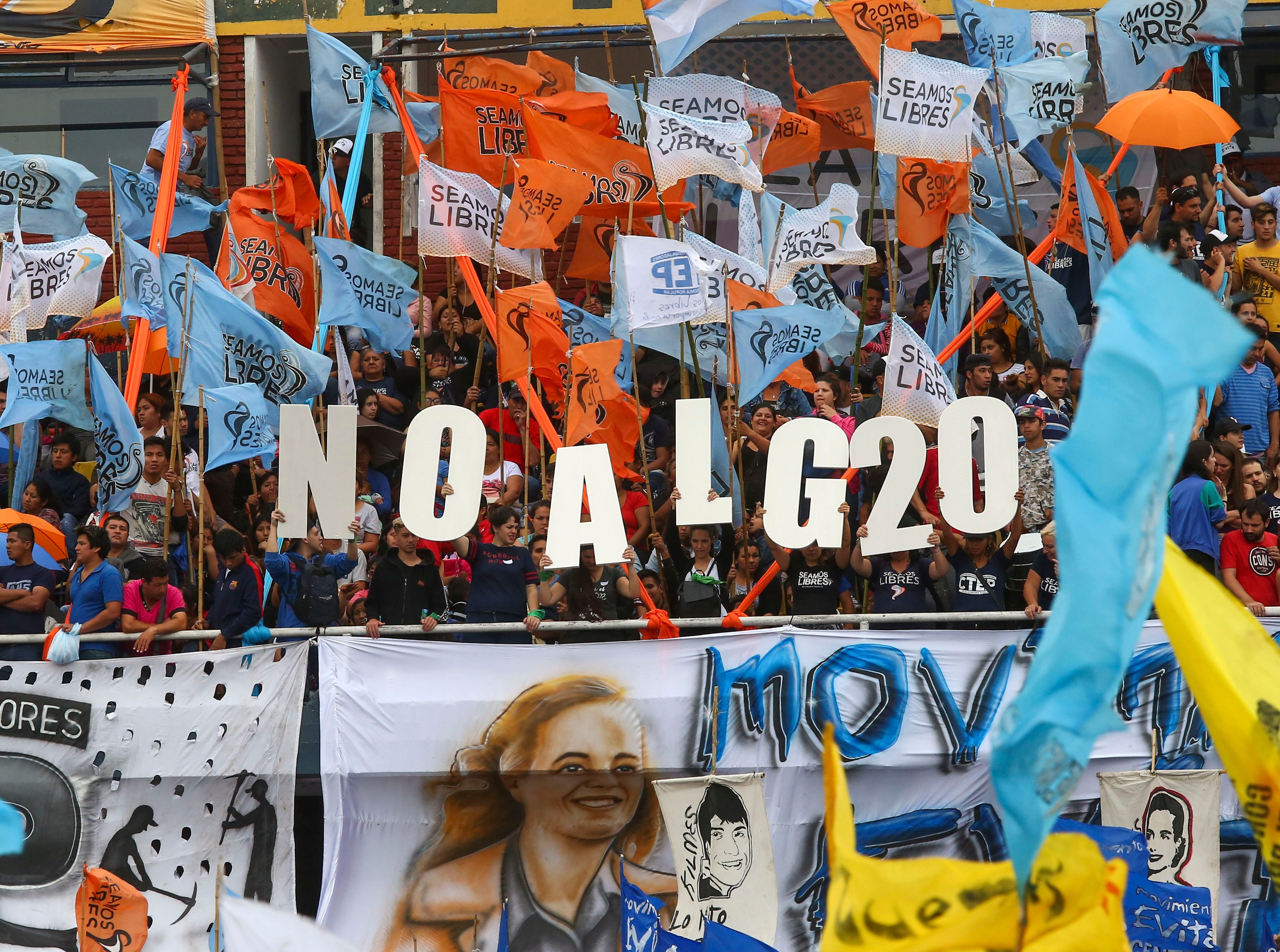 """BUENOS AIRES, ARGENTINA - NOVEMBER 27: Demonstrators wave flags and hold letters that read in Spanish """"No to G20"""" during a protest against G20 organized by Communist Party and social organizations at Leon Kolbowsky Stadium on November 27, 2018 in Buenos Aires, Argentina. (Photo by Nacho Sanchez/Getty Images)"""