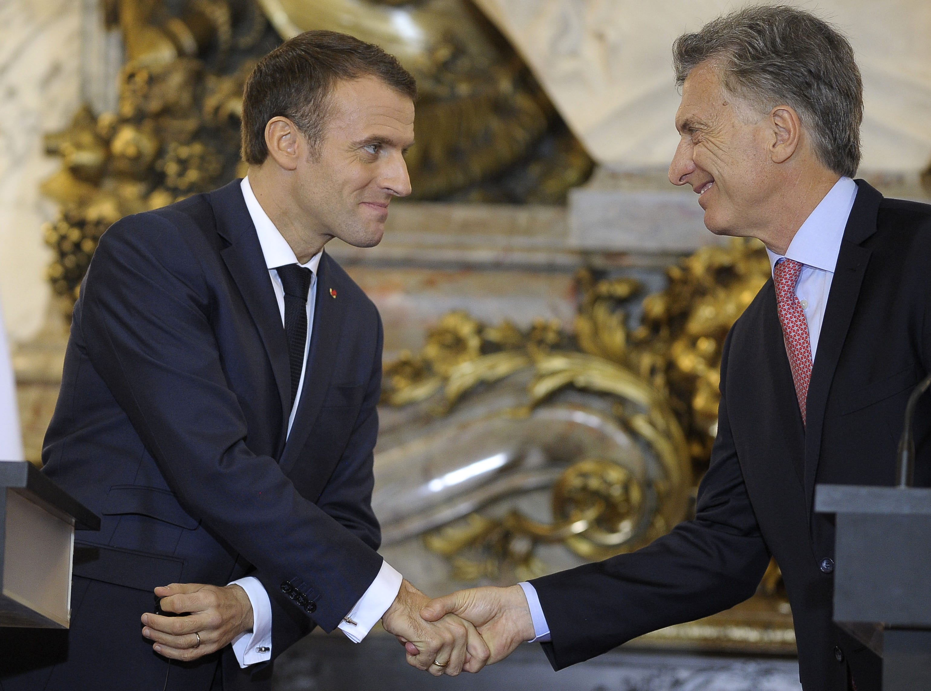"""France's President Emmanuel Macron (L) shakes hands with Argentina's President Mauricio Macri during a press conference, at the Casa Rosada presidential palace in Buenos Aires, on November 29, 2018, on the eve of the G20 Leaders' Summit. - Macron arrived on the eve for a two-day G20 summit beginning on November 30 likely to be dominated by simmering international tensions over trade. In an interview with Argentine daily La Nacion, he warned against the risk of """"a destructive trade war for all"""" emanating from the G20 discussions. (Photo by JAVIER GONZALEZ TOLEDO / AFP)        (Photo credit should read JAVIER GONZALEZ TOLEDO/AFP/Getty Images)"""