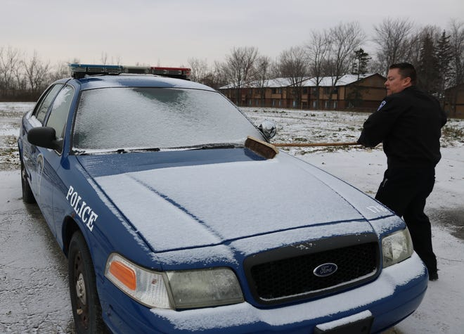 Officer Mark Anderson, of the Port Clinton Police Department, sweeps off snow from this 2004 Ford Crown Victoria cruiser.