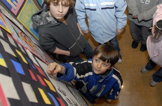Cameron Hinojosa, a second grader at Sparlingville Elementary School, reaches up to explain his art work to family during the 39th annual Beatrice Thornton Student Art Exhibition Thursday afternoon in the Fine Arts Building at St. Clair County Community College. The nonjuried show held in honor of Beatrice Thornton, an art teacher dedicated to her students, started at the Port Huron Museum in 1968. Times Herald photo by Wendy Torello.