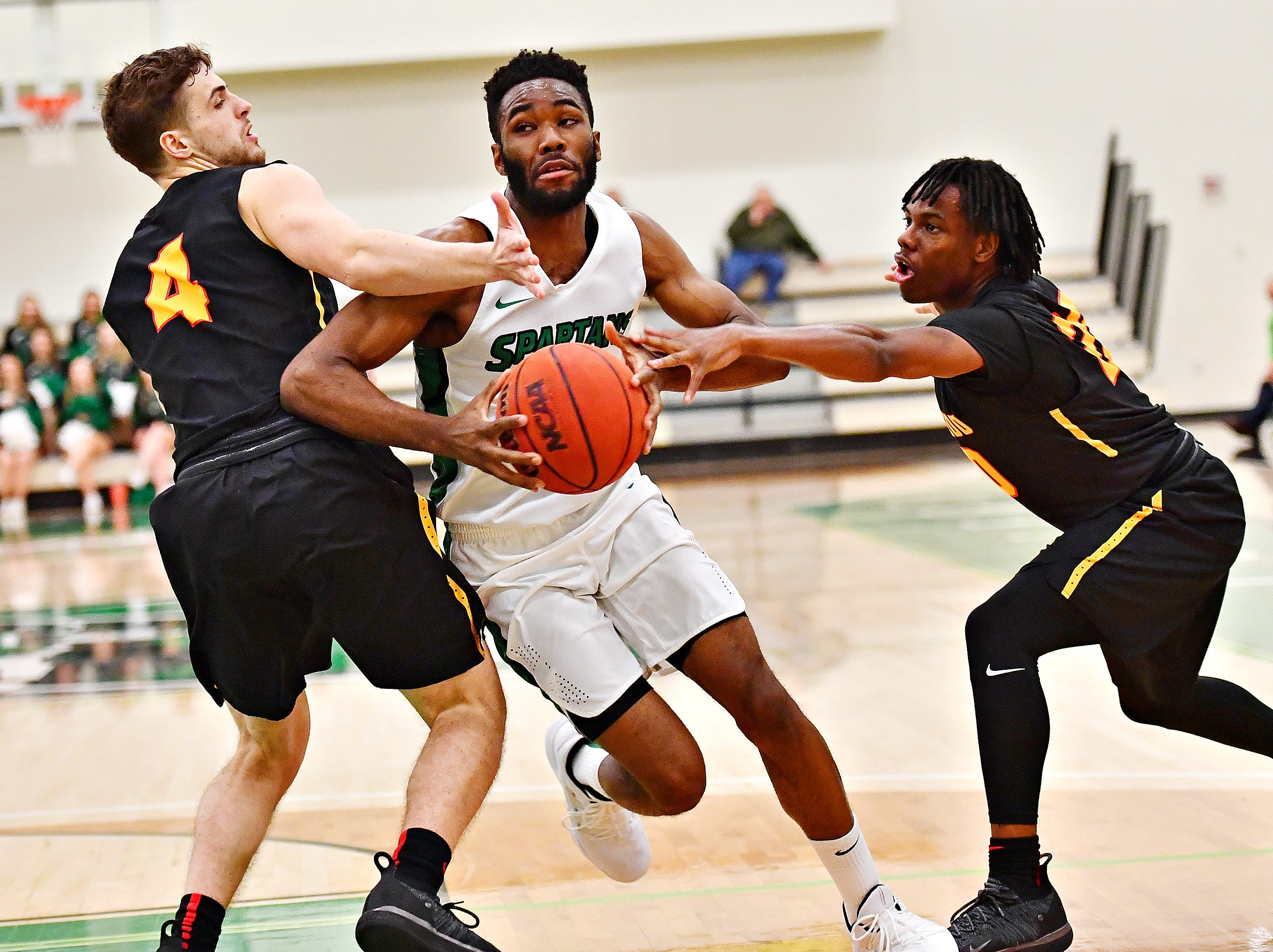 York College's Jason Bady, center, gets past Gwynedd-Mercy's Matt Sommers, left, and Clayton Wolfe during men's basketball action at Grumbacher Sport and Fitness Center in Spring Garden Township, Wednesday, Nov. 28, 2018. Dawn J. Sagert photo