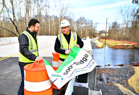 Project Engineer Nathan Elliott, left, of Plenary Group, and Public Information Manager Jeff Rossi, of Walsh Group and both with the PA Rapid Bridge Replacement project, prepare a sign for display as Plenary Walsh Keystone Partners hold a ribbon-cutting ceremony to commemorate the opening of the 500th bridge for the project, located on Andersontown Road, spanning Yellow Breeches Creek into both Fairview and Lower Allen Townships, Thursday, Nov. 29, 2018. Dawn J. Sagert photo