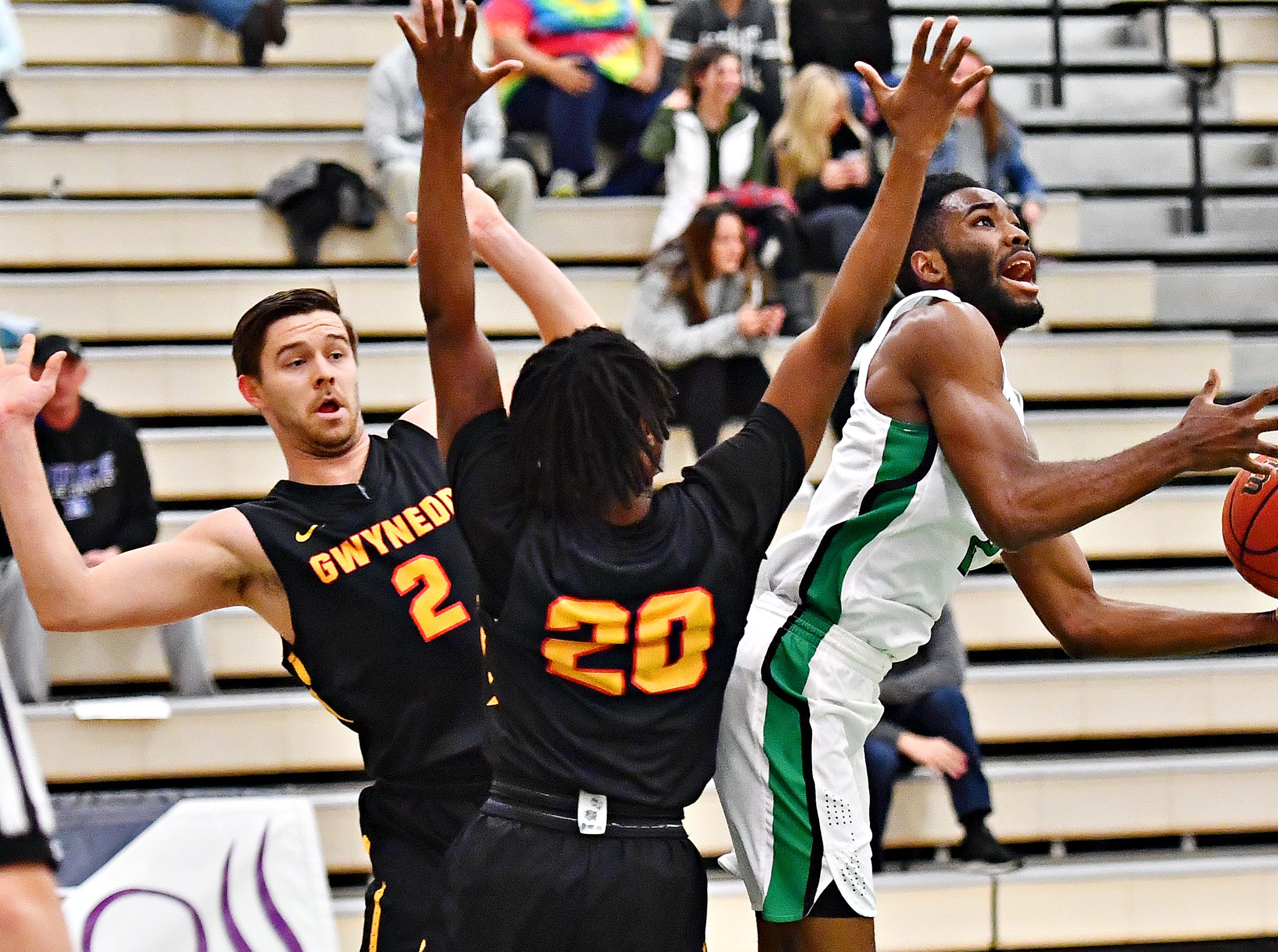 York College's Jason Bady, right, pushes past Gwynedd-Mercy's Jeff Seigafuse, left, and Clayton Wolfe during men's basketball action at Grumbacher Sport and Fitness Center in Spring Garden Township, Wednesday, Nov. 28, 2018. Dawn J. Sagert photo