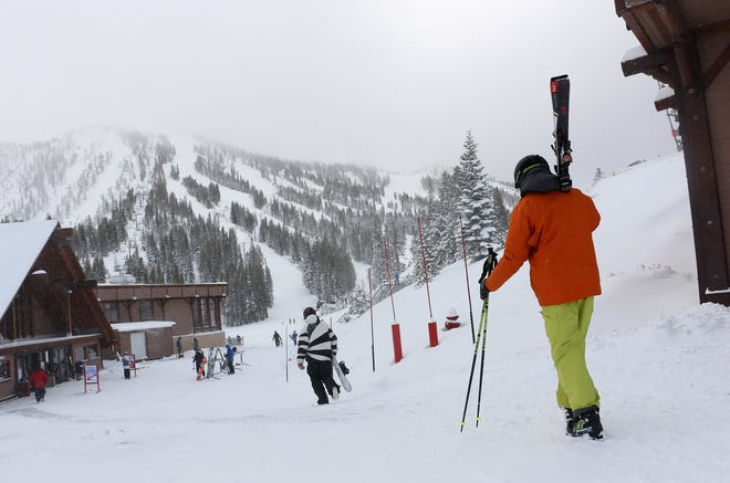 Skiers and snowboarders walk to the lifts at Mt. Rose Ski Tahoe near Reno on Nov. 29, 2018.