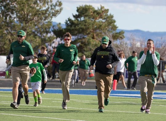 Ernie Howren runs with the Bishop Manogue assistant coaches last Saturday at the state semifinal football game at McQueen.