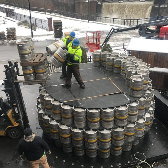 Workers place half-barrel kegs Thursday on the fifth of what would become 12 layers for this year's Genesee Brewery keg tree at the Genesee Brew House.