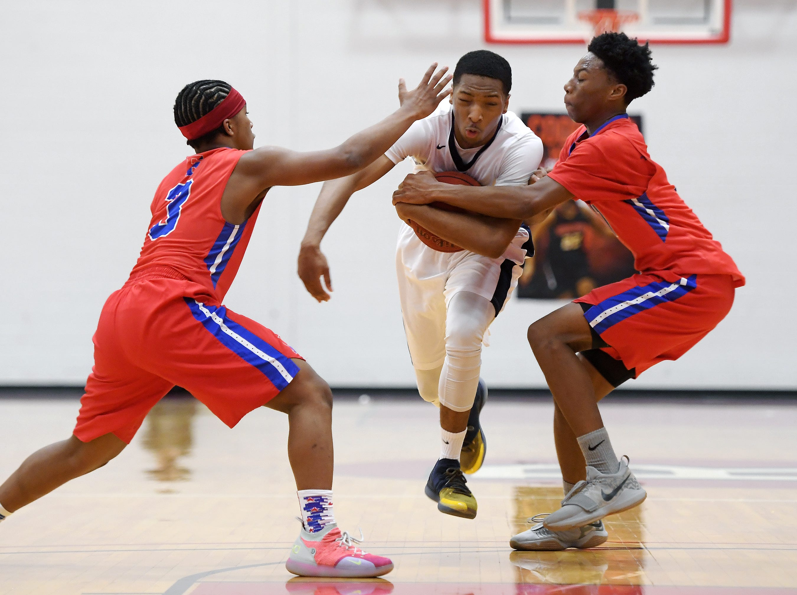 University Prep's Na'Zea Fowlks, center, splits the defense of Fairport's Andre Starks, left, and Vanzell Johnson during a regular season game played at Roberts Wesleyan College on Wednesday, Nov. 28, 2018. Fairport beat University Prep 56-51.