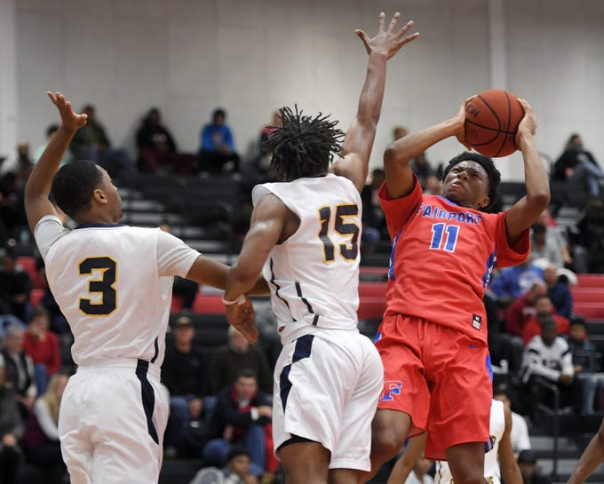 Fairport's Vanzell Johnson, right, takes a shot over the defense of University Prep's Jakhi Lewis (15) and Kayshawn Ross during a regular season game played at Roberts Wesleyan College on Wednesday, Nov. 28, 2018. Fairport beat University Prep 56-51.