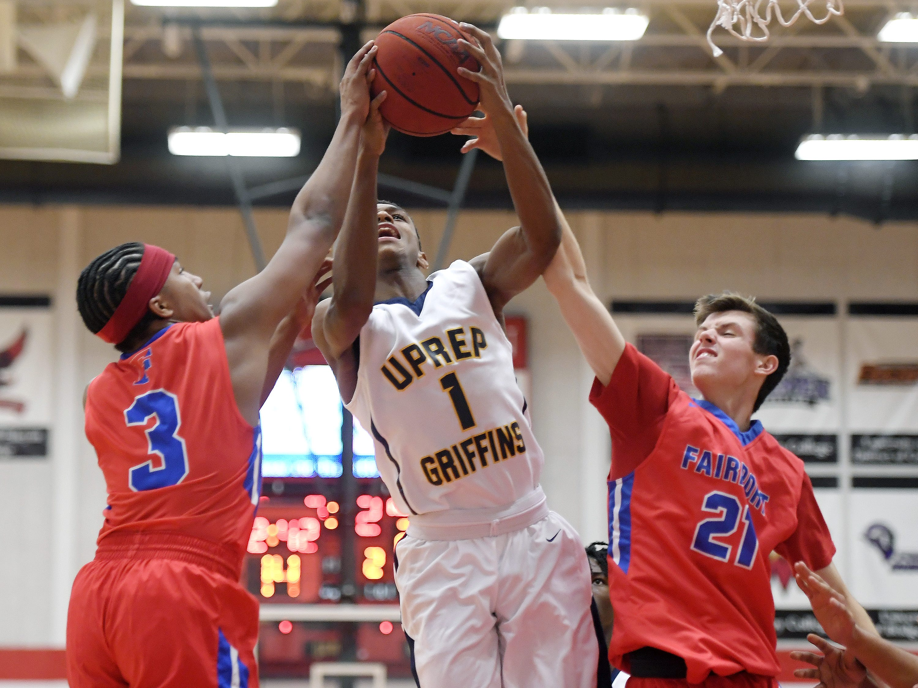 University Prep's Na'Zea Fowlks, center, grabs a rebound between Fairport's Andre Starks, left, and Max Molisani during a regular season game played at Roberts Wesleyan College on Wednesday, Nov. 28, 2018. Fairport beat University Prep 56-51.