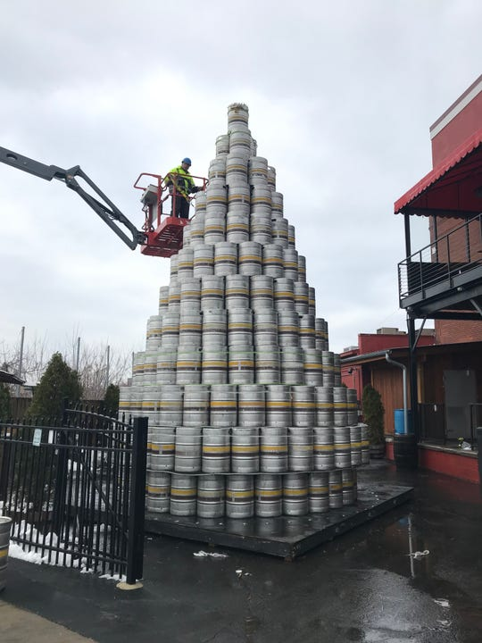Workers construct the Genesee Brewery keg tree Thursday at the Genesee Brew House.