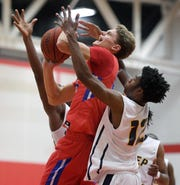 Fairport's Brett Heininger, top, is defended by University Prep's Krystain Lee during a regular season game played at Roberts Wesleyan College on Wednesday, Nov. 28, 2018. Fairport beat University Prep 56-51.
