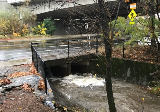 Water rushes into a storm drain off Park Marina Drive Thursday in Redding.
