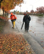 Ryan Nixa, left, and Jeffrey Horton, both of Forest Design, clear a sidewalk of rain-soaked leaves in November 2018 off Dana Drive in Redding.