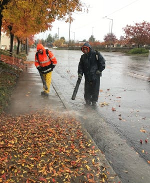 Ryan Nixa, left, and Jeffrey Horton, both of Forest Design, clear a sidewalk of rain-soaked leaves Thursday off Dana Drive in Redding.