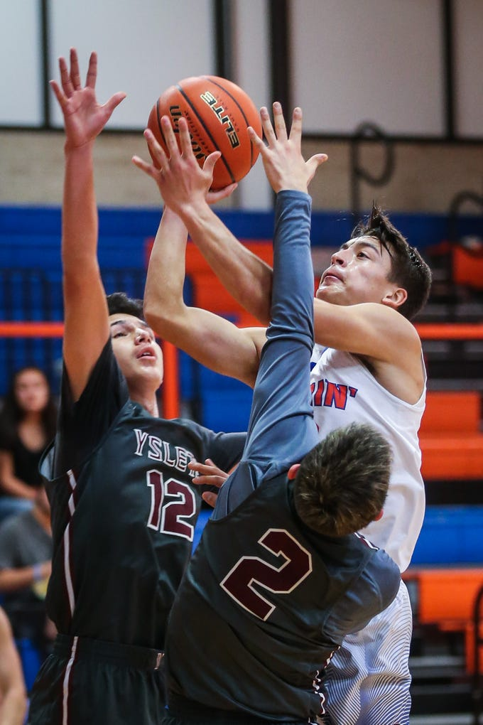 Central's Tristan Lopez attempts to shoot the ball as Ysleta blocks during the Doug McCutchen Basketball Tournament Thursday, Nov. 29, 2018, at Central High School.