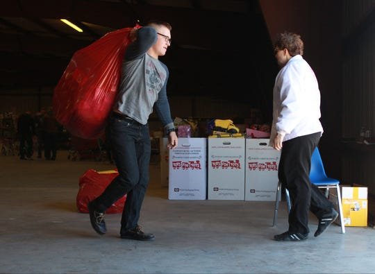 Marine Bailee Whited from Goodfellow Air Force Base carries a large plastic bag filled with Christmas gifts to a San Angelo family in 2015.