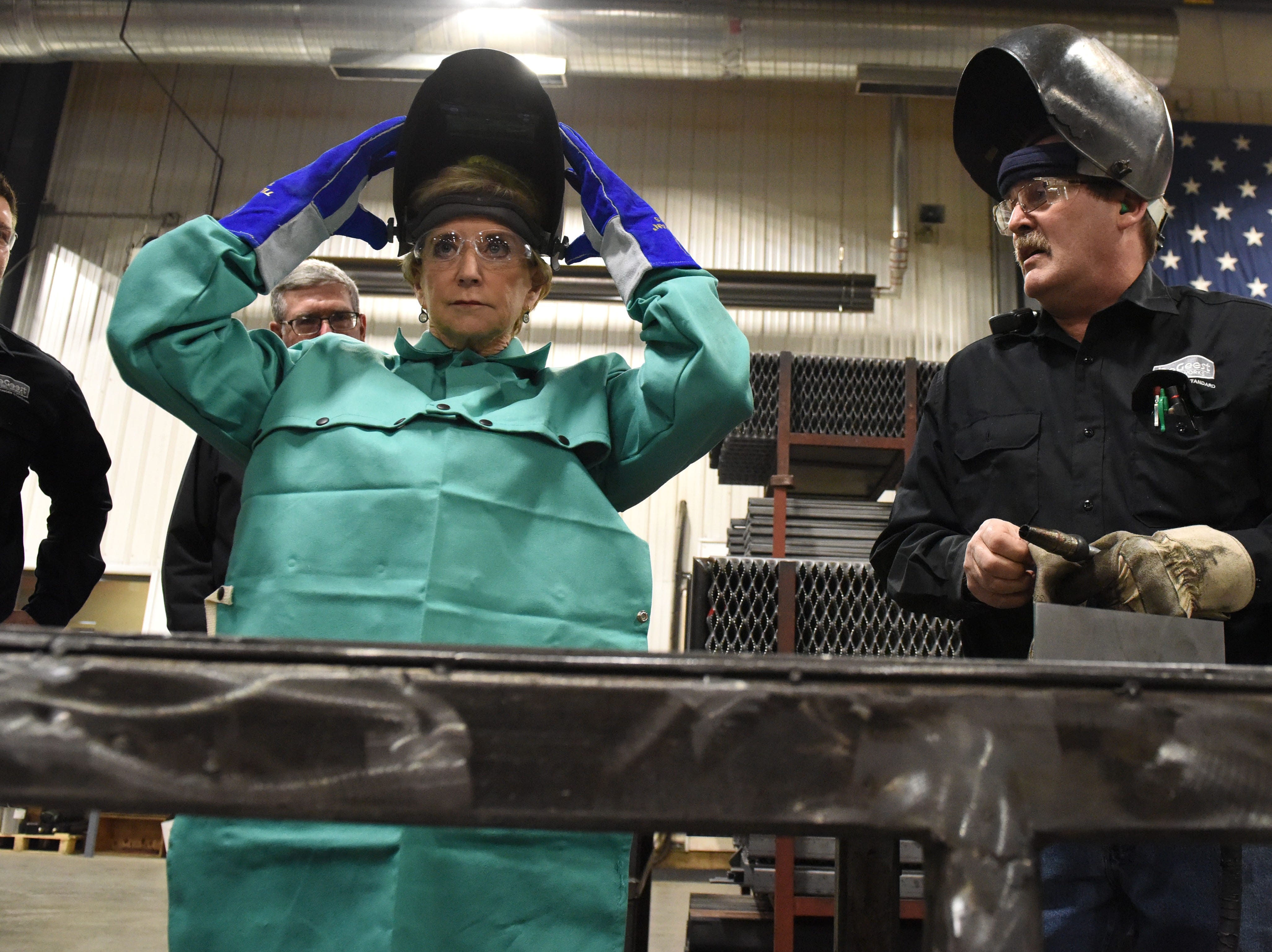 Linda McMahon, head of the U.S. Small Business Administration, gets ready to weld at DeGeest Steel Works in Tea, S.D., Thursday, Nov. 29, 2018.