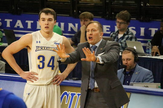 Alex Arians talks with coach TJ Otzelberger during SDSU's win over Kansas City Wednesday night in Brookings