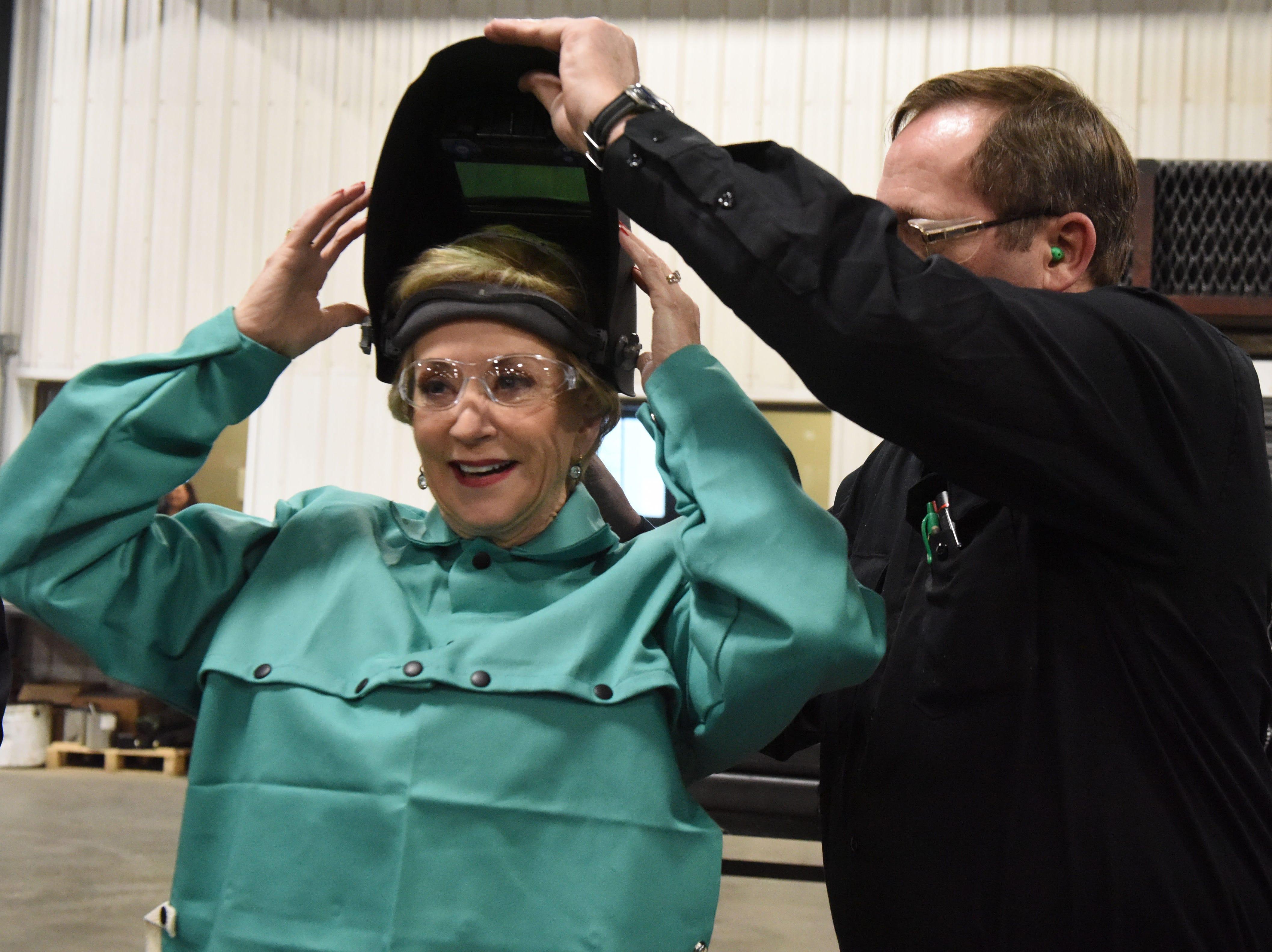 Dennis Roozenboom, welding supervisor, helps Linda McMahon, head of the U.S. Small Business Administration, put on her welding helmet at DeGeest Steel Works in Tea, S.D., Thursday, Nov. 29, 2018.