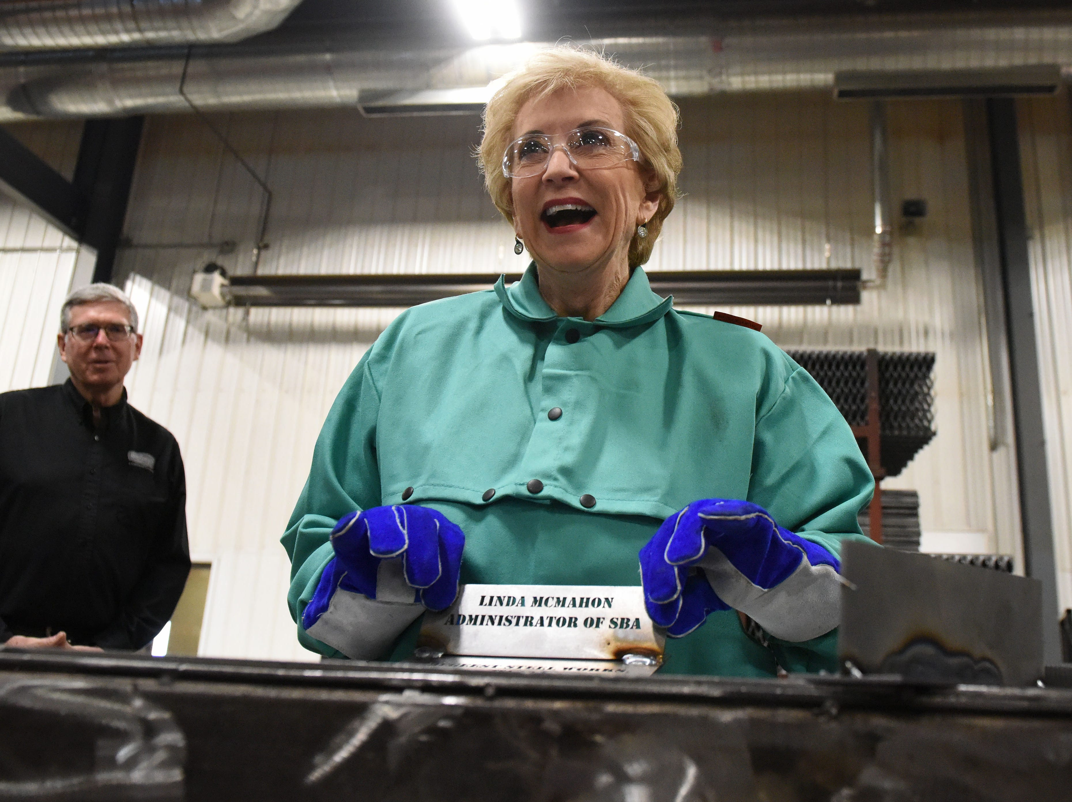 Linda McMahon, head of the U.S. Small Business Administration, shows off what she welded at DeGeest Steel Works in Tea, S.D., Thursday, Nov. 29, 2018.