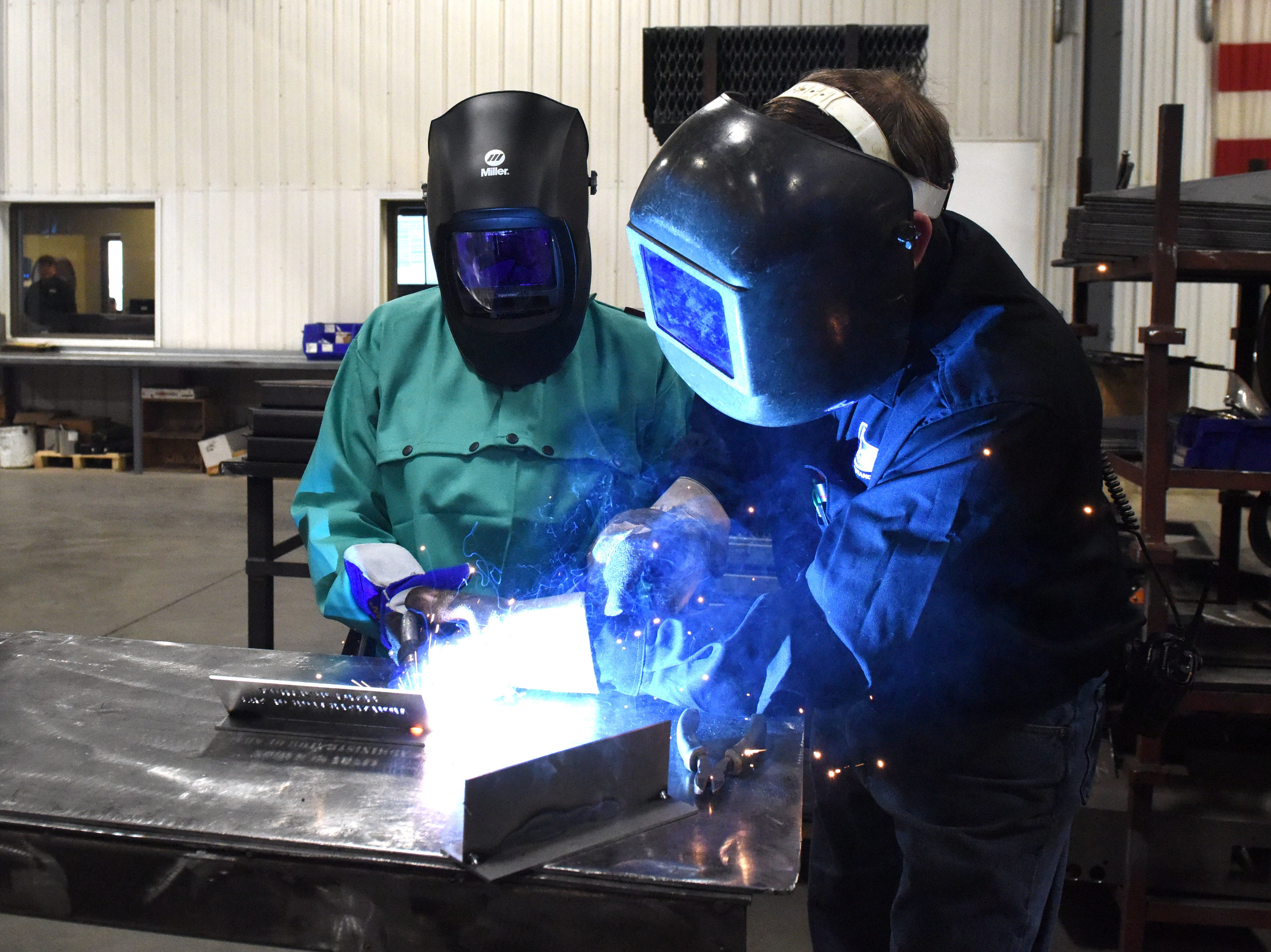 Dennis Roozenboom, welding supervisor, and Linda McMahon, head of the U.S. Small Business Administration, weld at DeGeest Steel Works in Tea, S.D., Thursday, Nov. 29, 2018.