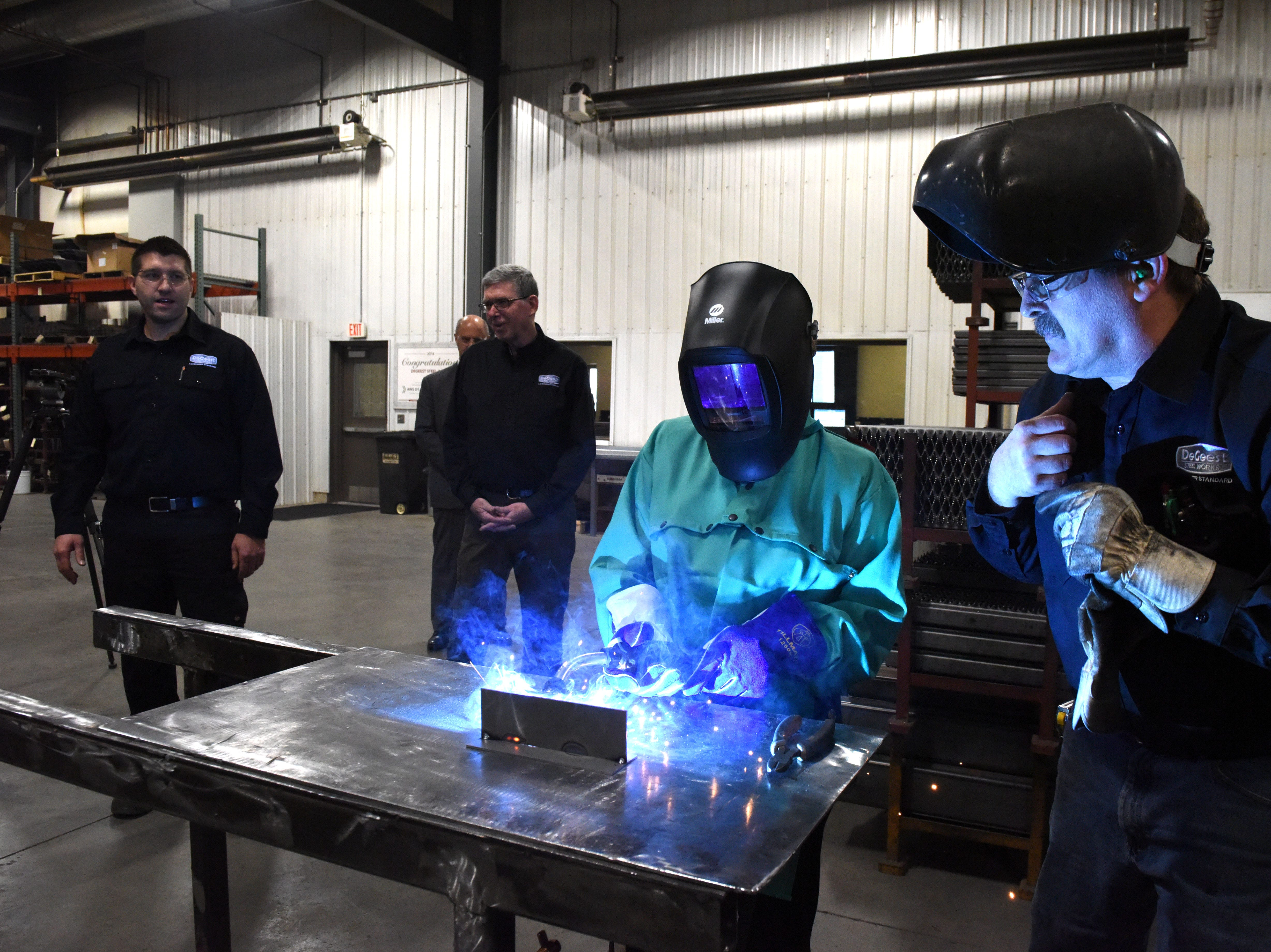 Linda McMahon, head of the U.S. Small Business Administration, welds at DeGeest Steel Works in Tea, S.D., Thursday, Nov. 29, 2018.