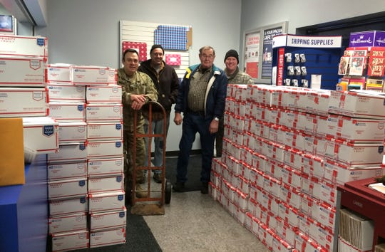 Local troops and volunteers pose for a photograph after unloading more than 300 care packages for soldiers serving overseas Thursday, Nov. 29, at the Waite Park post office.