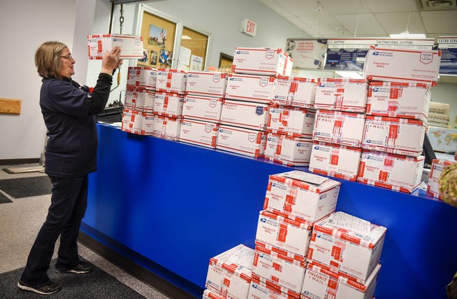 Becky Carlson stacks care packages to be mailed to U.S. troops serving overseas Thursday, Nov. 29, at the Waite Park post office. More than 300 boxes, with each containing more than 50 items, were sent Thursday.